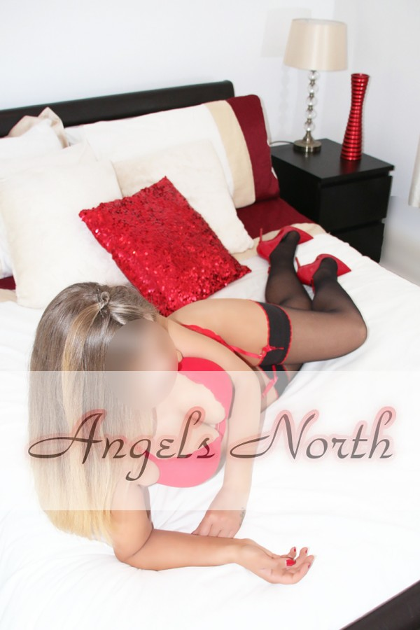 Slim blonde in red on bed